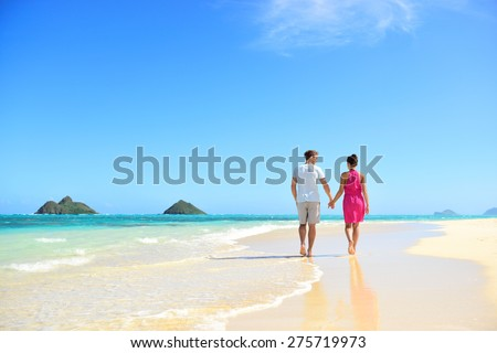Beach honeymoon couple holding hands walking on white sand beach. Newlyweds happy in love relaxing on summer holidays on Lanikai beach, Oahu, Hawaii, USA with Mokulua Islands. Travel vacation concept. - stock photo