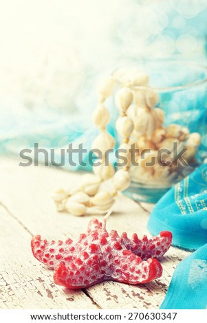 beach house decor, setting summer vacation : Candle in the form of starfish, shells, pareo on the wooden background  (Toning, bokeh) - stock photo