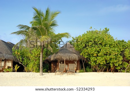 beach hut under palm trees - stock photo