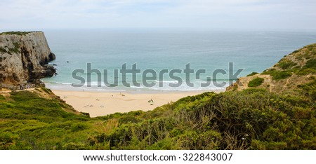 Beach in Algarve region of Portugal in cloudy day. People swimming and surfing. A view from the top - stock photo
