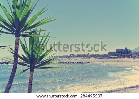 Beach in luxurious Spanish seaside resort Puerto Banus, located close to Marbella, on a sunny summer day. Filtered image in faded, washed-out, retro style; summer travel vintage concept. - stock photo