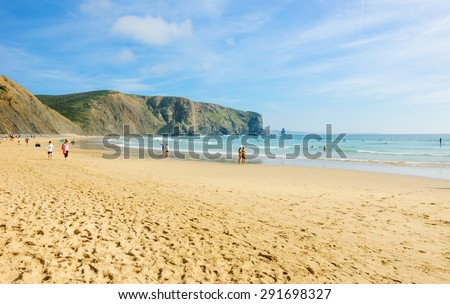 Beach in the Algarve region of Portugal. People swimming and surfing.  - stock photo
