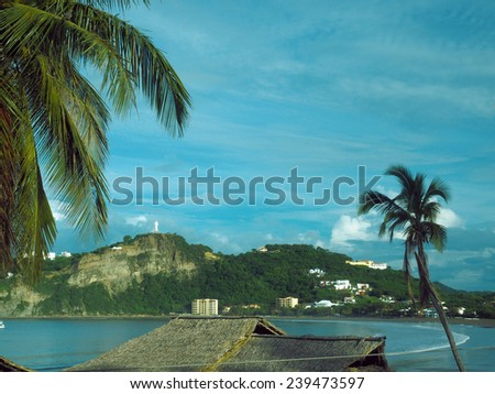 beach landscape resort town  San Juan del Sur Nicaragua with landmark statue Jesus Christ on mountain on Pacific Ocean Central America - stock photo