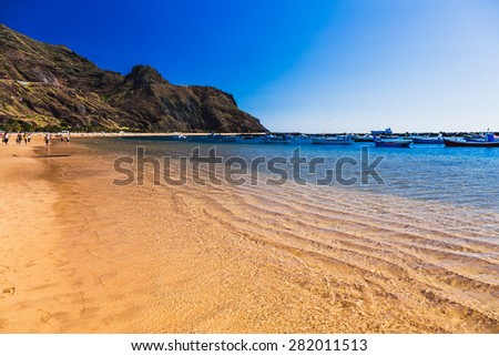 Beach Las Teresitas with water and waves on yellow sand on coast or shore of Atlantic ocean on Tenerife Canary island, Spain. Mountain at the background - stock photo