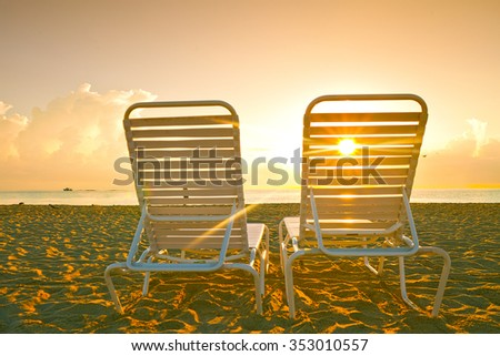 Beach lounge chairs in Miami Florida at sunrise - stock photo