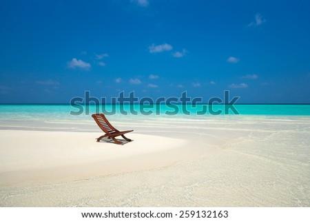 Beach lounger on sand beach. - stock photo