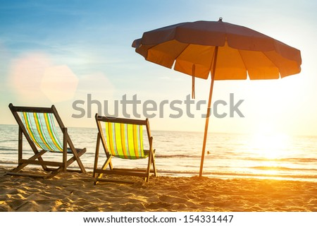 Beach loungers on deserted coast sea at sunrise - stock photo