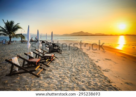 beach loungers on the sea at sunrise, Thailand - stock photo