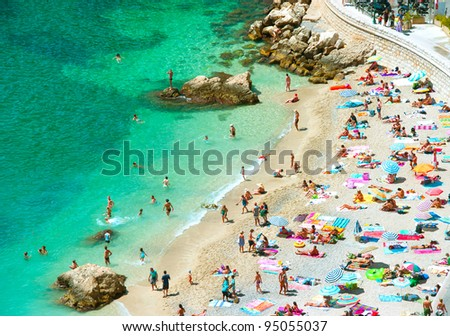 beach of the Cote d'Azur with tourists with sunbeds and umbrellas on the hot summer day - stock photo