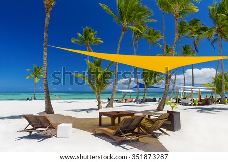 Beach on the tropical island. Clear blue water, sand and palm trees. Beautiful vacation spot, treatment and aquatics. - stock photo