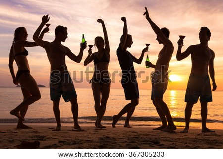 beach party, group of young people dancing, friends drinking beer and cocktails at sunset - stock photo