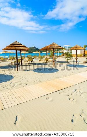 Beach path and sun umbrellas on beautiful sandy Villasimius beach, Sardinia island, Italy - stock photo