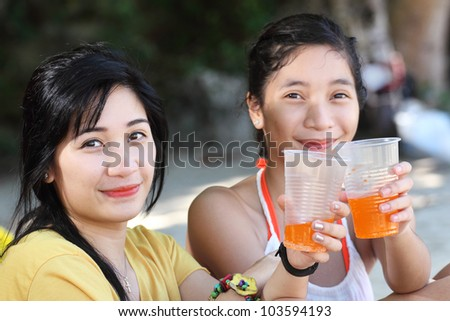 Beach portrait of two ladies holding a plastic cup with orange juice. - stock photo