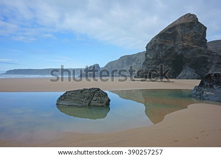 Beach Reflections of rock pool and sea stacks at Bedruthan Steps on a winter day, North Cornwall, UK - stock photo