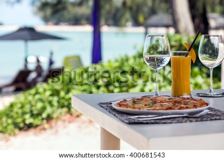 Beach restaurant with sea view, glasses, plates, food, tropical cocktail with mango and pizza Margarita - stock photo