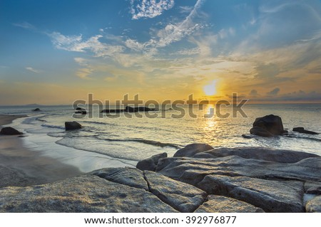 Beach rock and wave with sunrise skies background - stock photo