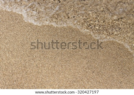 Beach sand background with water waves - stock photo