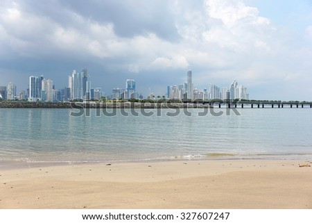 Beach sand in foreground with the new highway over the bay and Panama city skyscrapers in background, Panama, Central America - stock photo
