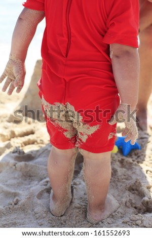 Beach sand on baby swimming suit - stock photo