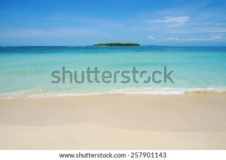 Beach sand with turquoise water and a tropical island at the horizon, Caribbean sea, Bocas del Toro, Cayos Zapatilla, Panama - stock photo