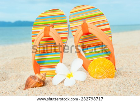 Beach sandals or tongs on a sandy beach - stock photo