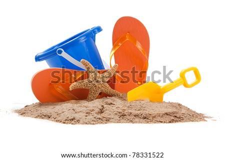 Beach scene with blue pail, orange flip-flops, starfish and a yellow shovel - stock photo