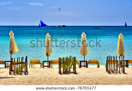 Beach Scene with Sail Boats and lounging chairs overlooking a clear blue sea. - stock photo