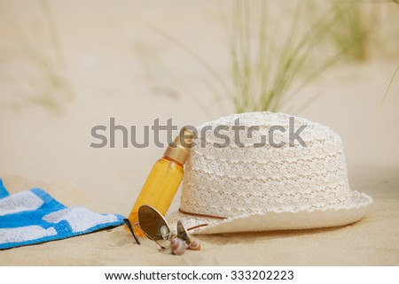 Beach set summer hat sunglasses and skin lotion lying on the sand.. All you need to resting and relax - stock photo
