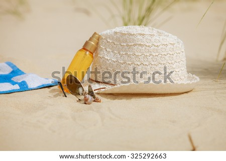 Beach set summer hat sunglasses and skin lotion lying on the sand. Vacation resting and relax - stock photo