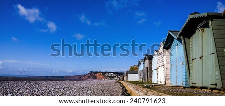 Beach shacks at Exmouth beach, Devon, United Kingdom, showing various beach shacks next to the sea - stock photo