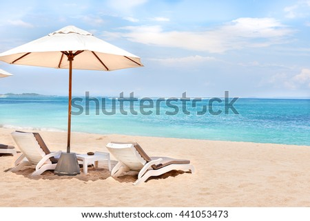 Beach side rest chairs and umbrellas on the sand near the blue water and horizon - stock photo