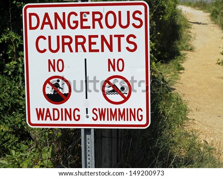 Beach sign that says, Dangerous Currents, No Swimming or Wading. - stock photo