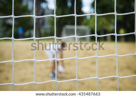 Beach soccer player through the net. Rio olympic games. - stock photo