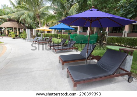 Beach sofa with umbrella beside swimming pool - stock photo