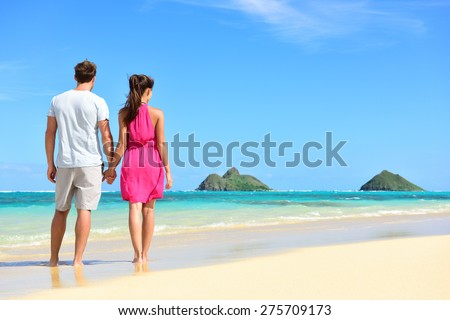 Beach summer holiday - couple on Hawaii beach vacation standing in white sand relaxing looking at ocean. Romantic young adults holding hands on Lanikai beach, Oahu, Hawaii, USA with Mokulua Islands. - stock photo