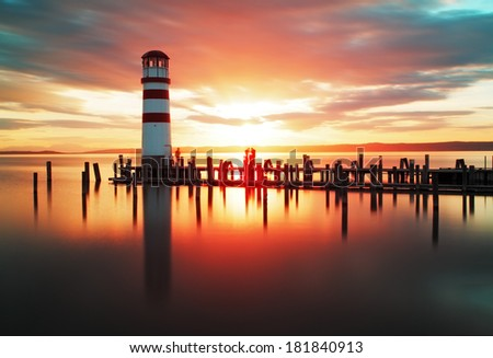 Beach sunset with lighthouse - stock photo