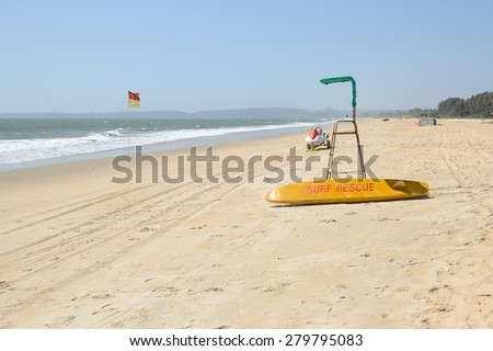 Beach Surf Rescue surfboard, flag and chair. - stock photo