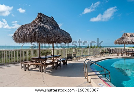 Beach table with hay parasol next to a swimming pool, on a sunny summer day - stock photo
