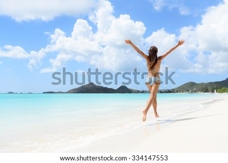 Beach, travel and vacation holidays concept with bikini girl happy running full of joy and aspiration on pristine beautiful Caribbean beach with turquoise water. Woman on Jolly Beach, Antigua. - stock photo