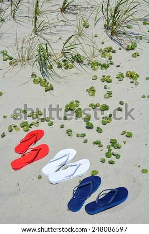 Beach travel concept. Red white and blue flip flops on the sand, perfect for cover art. - stock photo