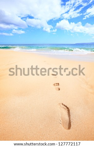 Beach travel vacation concept - footsteps in sand on beautiful sunny summer day during getaway holidays under the blue sky. From Makena beach, Maui, Hawaii - stock photo