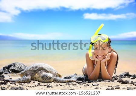 Beach travel woman on Hawaii with sea sea turtle. Snorkeling girl on vacation wearing snorkel smiling happy enjoying blue sky and sun lying next to Hawaiian sea turtles on Big Island, Hawaii, USA. - stock photo