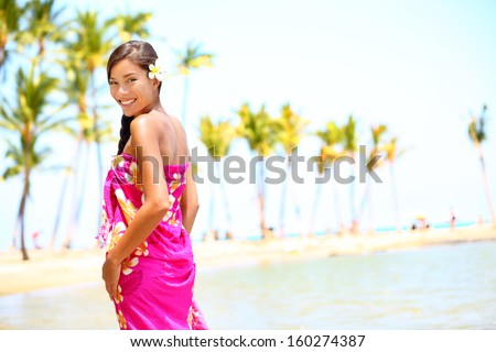 Beach travel - woman smiling happy on Hawaii. Girl in sarong cheerful on sunny hawaiian palm tree beach on holiday resort vacation. Big Island, Hawaii, USA. Multicultural Asian Caucasian female model. - stock photo