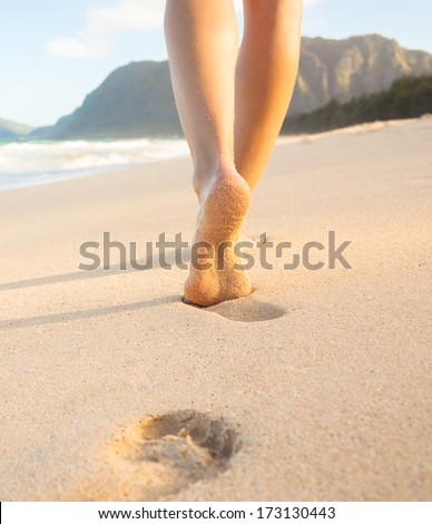 Beach travel - Woman walking on sand beach in Hawaii leaving footprints in the sand. - stock photo