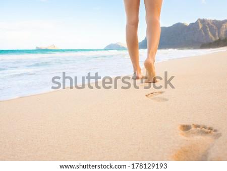 Beach travel - woman walking on sand beach leaving footprints in the sand. Closeup detail of female feet and golden sandy beach, Hawaii, USA. - stock photo
