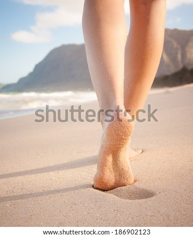 Beach travel - Woman walking on sand beach leaving footprints in the sand. Closeup detail of female feet and golden sand on beach in Hawaii, USA.  - stock photo