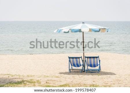Beach umbrella and beach chairs - stock photo