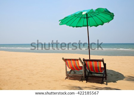 Beach umbrella and chairs on a deserted beach. - stock photo
