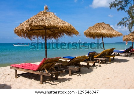 Beach umbrella and deck chairs on the beach - stock photo