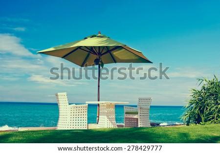Beach Umbrella And Sunbath Seats In A Tropical Beach Hotel That Located In Costal Area Negambo, Sri Lanka (With Instagram Effect) - stock photo